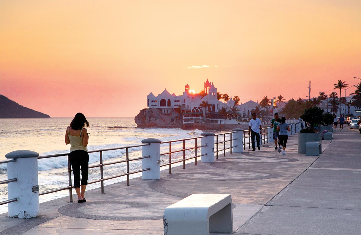 Mazatlan malecon at sunset with a girl on the back